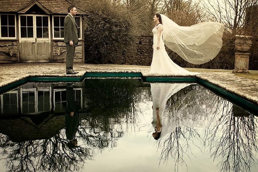 Wedding-photography-bride-groom-reflection-in-pool-white-veil-blows-in-wind.full