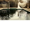 Wedding-photography-bride-groom-reflection-in-pool-white-veil-blows-in-wind.square