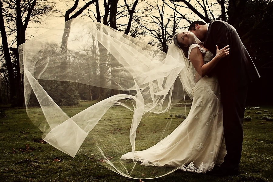 Wedding-photography-bride-leans-back-groom-holds-waist-outdoor-trees.full