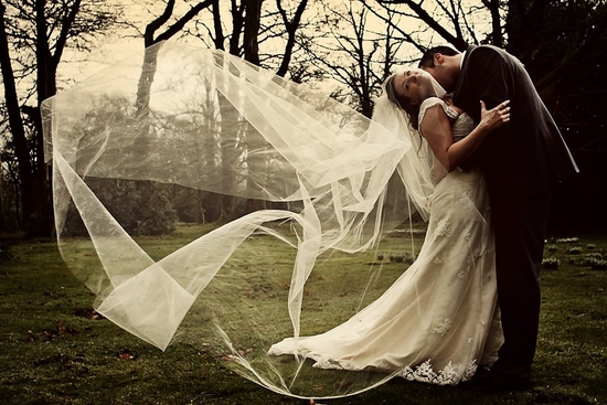 Bride arches back with white veil blowing in wind, groom holds her at waist