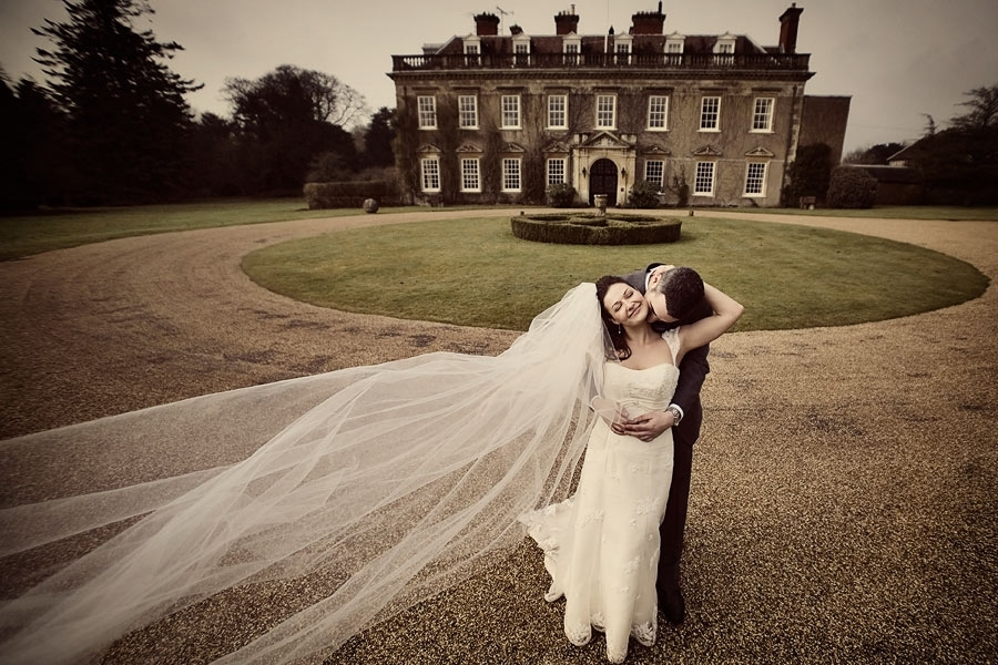 Wedding-photography-bride-n-groom-in-front-old-mansion-groom-kisses-neck.full