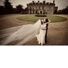 Wedding-photography-bride-n-groom-in-front-old-mansion-groom-kisses-neck.square