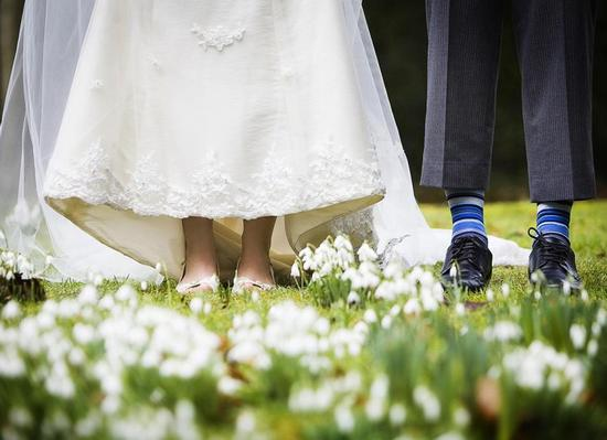 Artistic wedding photo- bride's bridal shoes and grooms blue socks, green grass with white flowersAr
