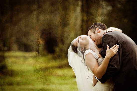 Bride and groom outside in forest, lean back while groom kisses neck