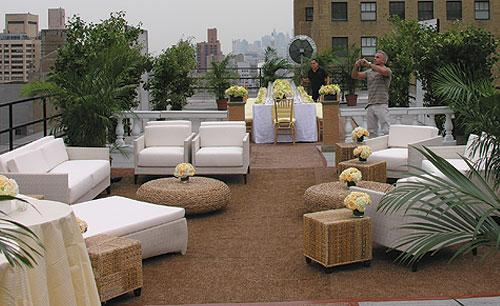 Ourdoor wedding on patio with white lounging couches and chairs, natural wicker round and end tables