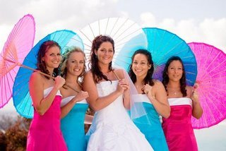 Fun, flirty colorful blue and pink parasols held by bridesmaids