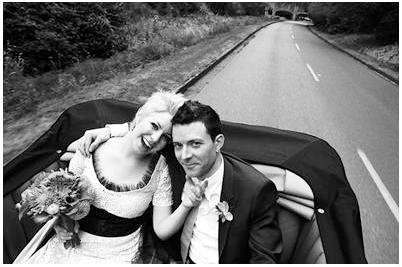 Bride and Groom take photos in vintage wedding car while driving down highway