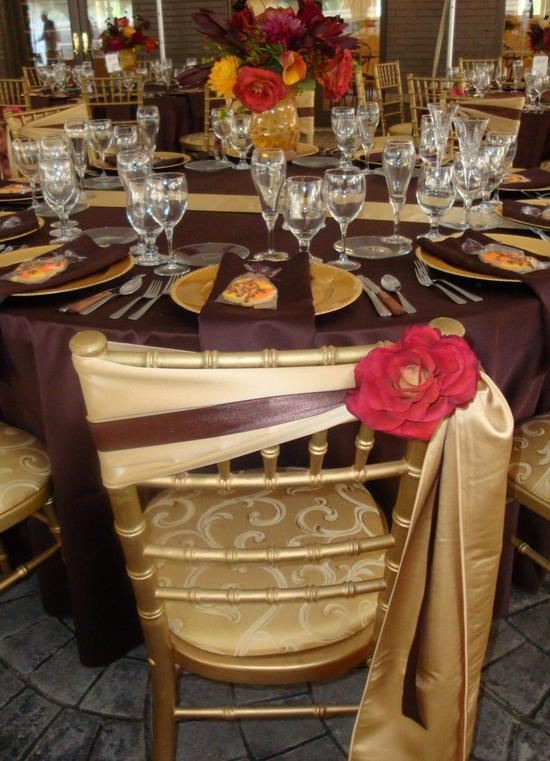 Beautiful burgundy and gold tablescape- gold charger plates, chairs, red flower