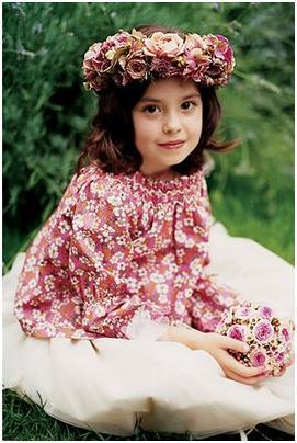 Beautiful flower girl with pink floral wreath on head, red and white floral shirt, white full skirt
