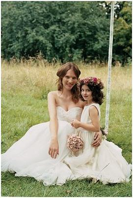 Beautiful bride in white strapless wedding dress with her cute flower girl