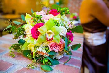 Beautiful, vibrant pink, leaf green, lime green, fuchsia, yellow bouquet set on bricks