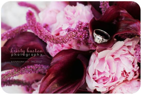 Closeup shot of purple, violet, lilac, pink bouquet with diamond engagement ring on top