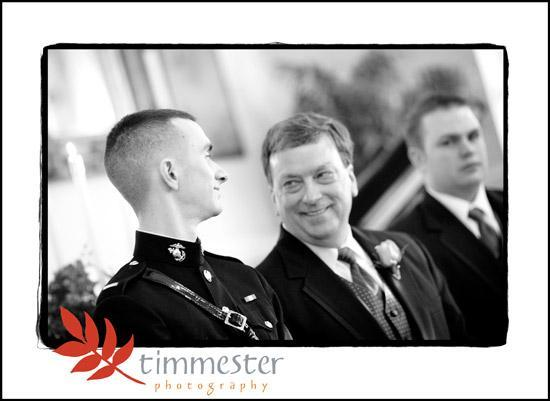 Groom in military attire smiles at his dad while awaiting beautiful bride to walk down aisle