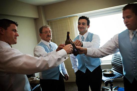Groom's father, groomsmen, best man, all in blue vest and tie, cheers with beer