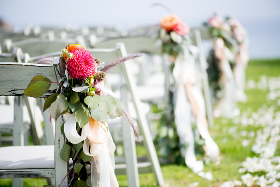 Hot pink dahlias and peach ribbons adorn ceremony chairs