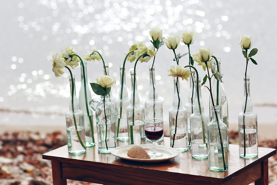 Glass bottles serve as vases for wedding reception centerpieces