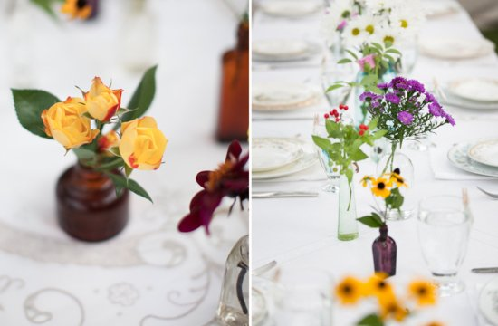 Vintage bottles hold bright wedding flowers