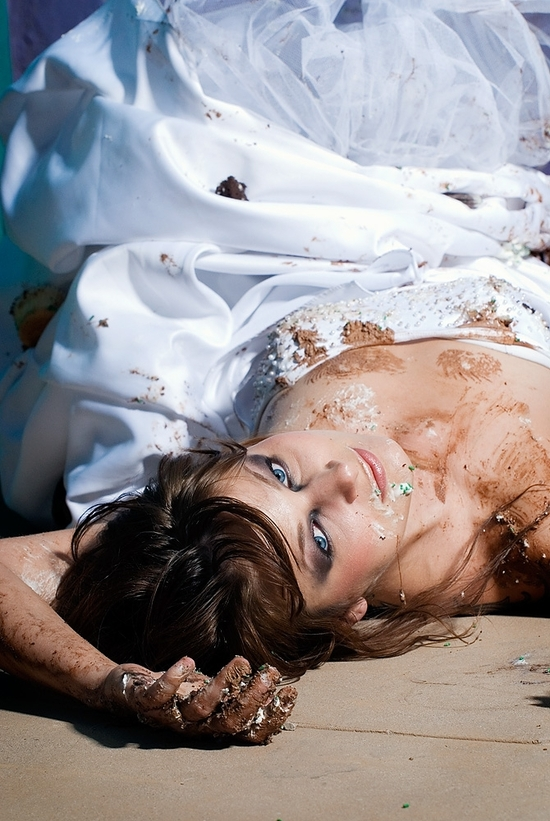 Post trash the dress- bride lays on ground in trashed white wedding dress