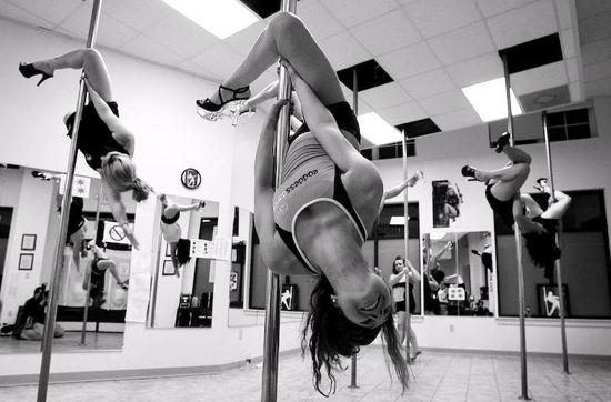 Black, white photo of bride and bridesmaids hanging upside down on poles during pole dancing lessons