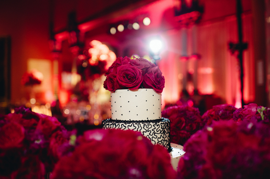 White and black wedding cake topped with deep pink roses