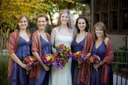 Bride in white wedding dress stands with bridesmaids (in navy), holding colorful floral bouquets