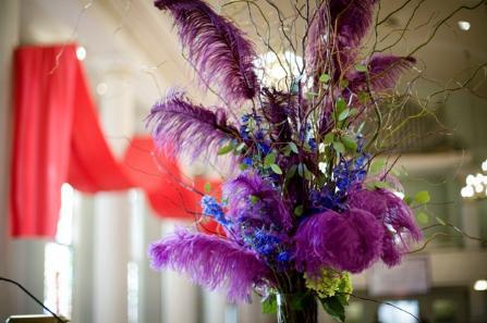 High table centerpiece with purple long feathers, blue flowers, green leafs and accents