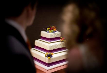 White wedding cake, purple ribbon, small floral details in yellow, red, orange, and green