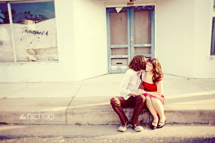 Engagement-photo-session-red-dress-bride-groom-sit-on-curb-groom-kisses-on-cheek.full