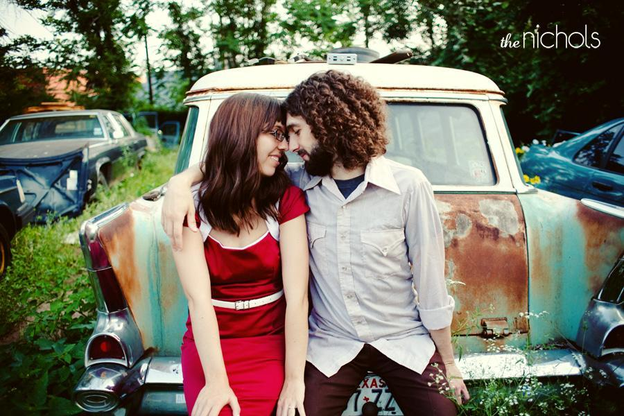 Engagement photo session, bride in red dress, couple sit on old truck in junk yard