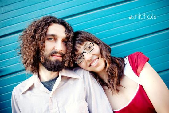 Happy engaged couple sit outside together in front of teal wall