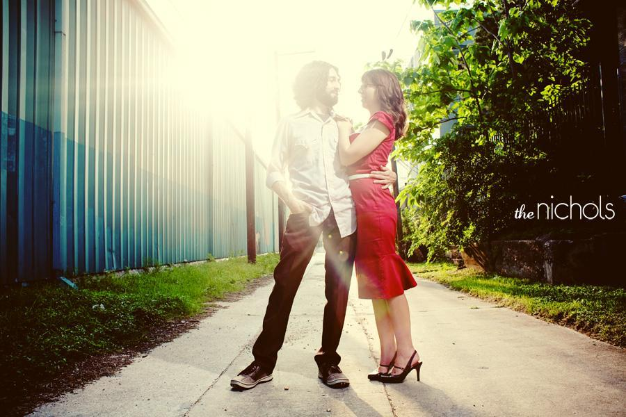 Engagement-photo-session-red-dress-bride-groom-pose-in-ally-outside-with-trees-and-sunlight-shining-down.full