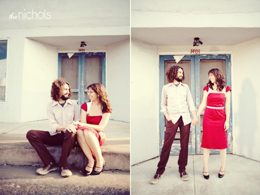 Engagement-photo-session-red-dress-bride-groom-sit-on-curb-smile-at-each-other-stand-holding-hands-in-front-of-blue-door.full
