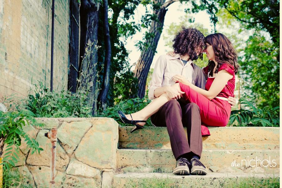 Engagement-photo-session-red-dress-bride-groom-sit-together-outside-on-steps.full