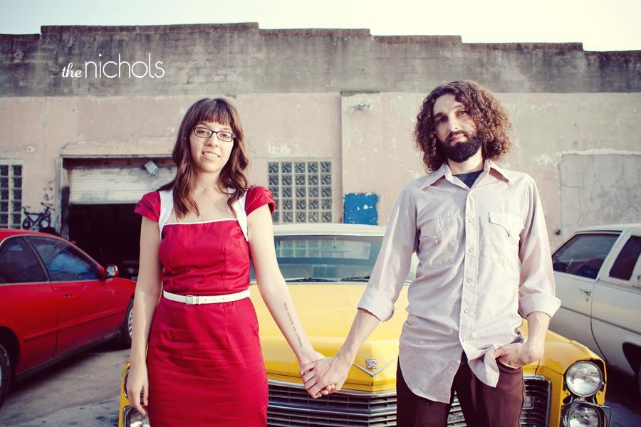 Engagement-photo-session-red-dress-hold-hands-in-front-of-yellow-vintage-cadillac.full