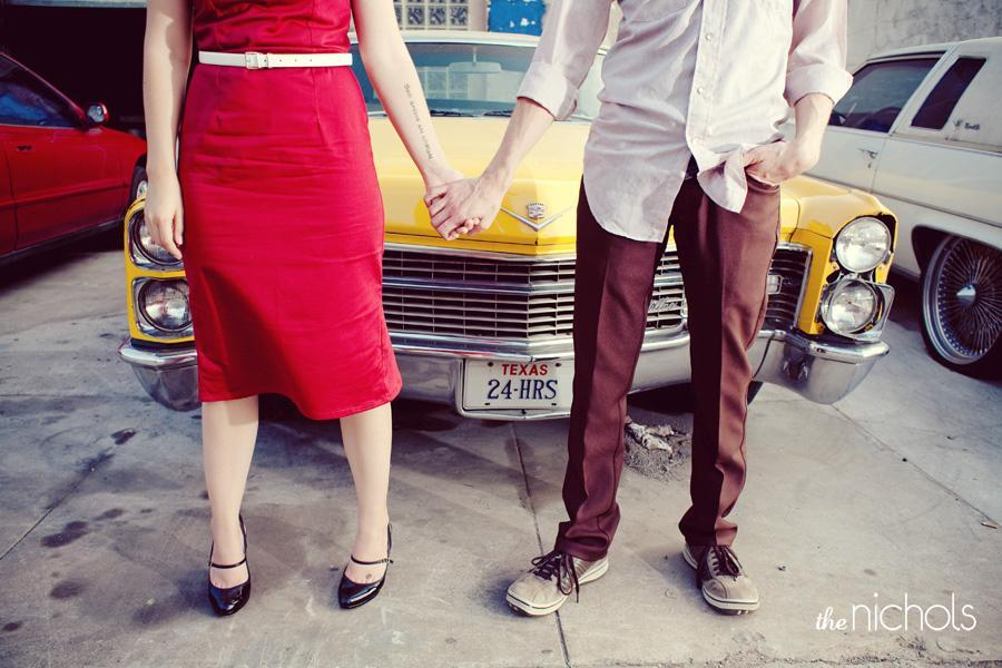 Engagement-photo-session-red-dress-hold-hands-in-front-of-yellow-vintage-cadillac-2.full