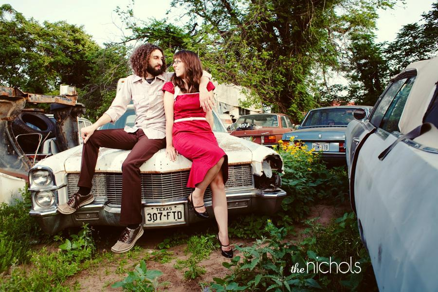 Engagement-red-dress-sit-on-white-vintage-car-outside-in-yard.full