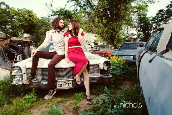Happy engaged couple sit on old vintage car in junk yard