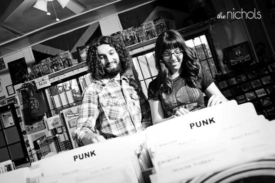 Edgy bride and groom at record store, black and white engagement shot