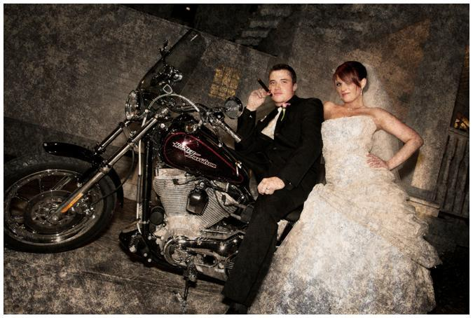 in white strapless wedding dress, and groom pose on Harley Davidson