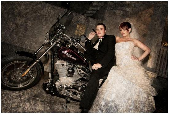 Bride, in white strapless wedding dress, and groom pose on Harley Davidson