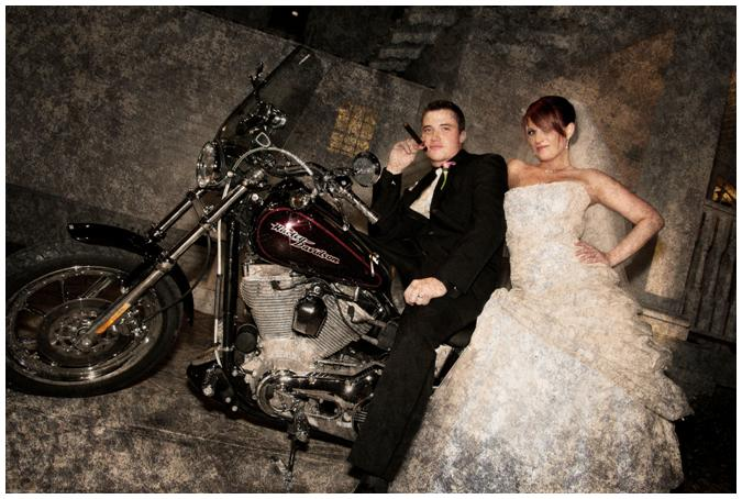 Bride In White Strapless Wedding Dress And Groom Pose On Harley Davidson