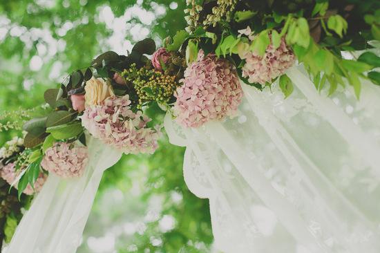 photo of Pink hydrangea adorned wedding arbor