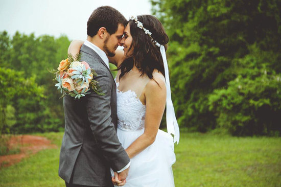 Bohemian bride holds succulent bouquet and handsome groom