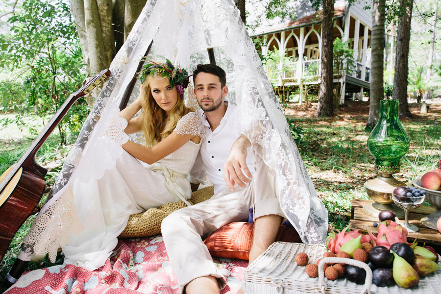 Boho-bride-and-groom-pose-beneath-lace-veil.full