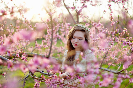 Hippie bride poses in cherry blossom tree