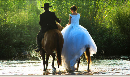 bride and groom ride horseback