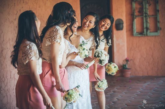California bride laughs with bridesmaids by her side