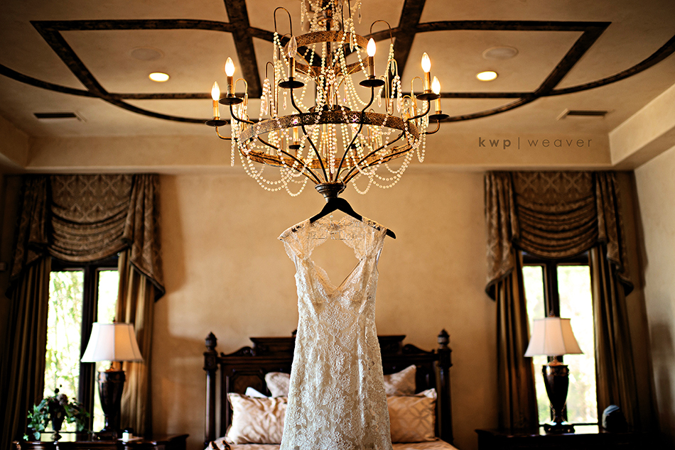 Lace-open-back-wedding-dress-hangs-on-chandelier.full