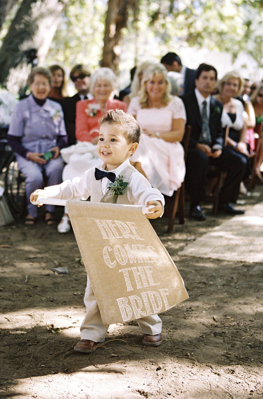Adorable ring bearer holds Here Comes the Bride Burlap Sign