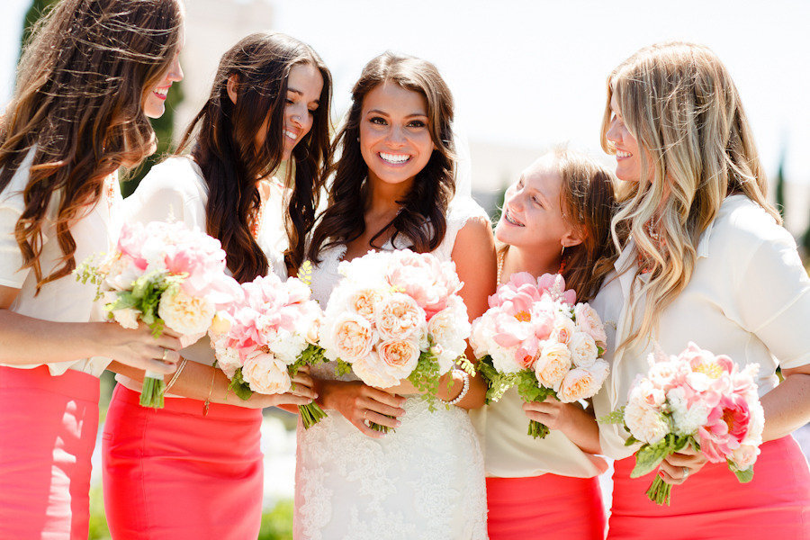Beach bride poses with bridesmaids in coral and ivory